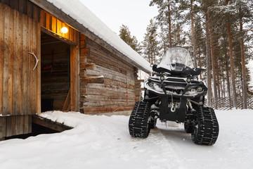 quad bike in winter near wooden houses Wall mural