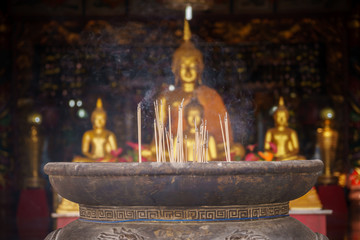 Smoke incense sticks in the pot with blur golden Buddha background