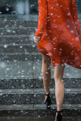 Legs and heels walking away in a colorful jacket, with falling snow