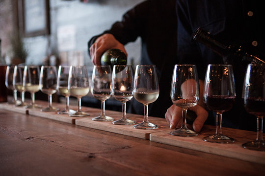 Row of wine glasses being poured with multiple types of wine