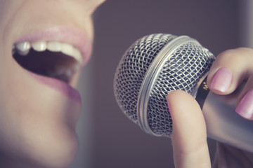 A woman sings into a microphone at a recording studio, her mouth close up.
