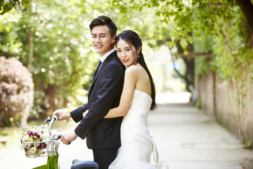 asian wedding couple riding bicycle