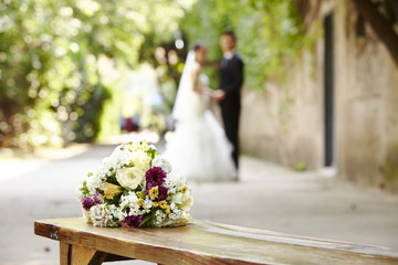 bouquet on wooden bench with young bride and groom in the background.