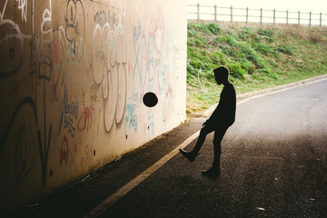 Silhouette of a boy kicking a ball against a tunnel wall.