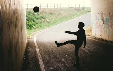 Silhouette of a boy kicking a ball against a tunnel wall.