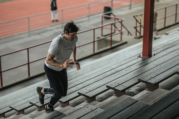 Young athletic man training by running stairs
