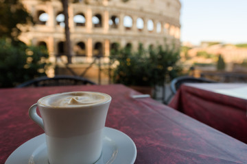 Italian cappuccino coffee cup on a table, with roman coliseum in background, at sunrise in Rome, Italy.