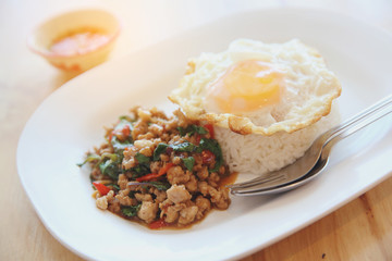 stir fried pork and basil with rice and egg on wood background thai food