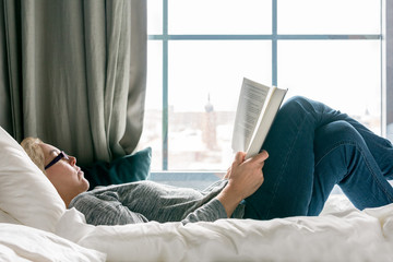 Relaxed woman with glasses lying on a bed reading a book beside a big window, profile view.