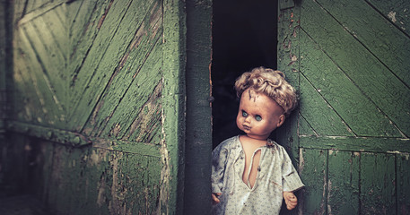 The old doll peeks out of the gate of the old garage. Horror, scary, Halloween.