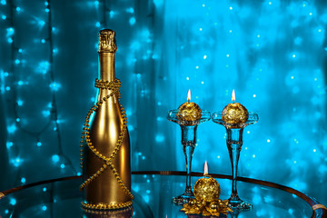 A bottle of champagne and candles in New year and Christmas on blue background