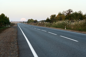 The full moon that leaves the horizon above the asphalt road in the early morning