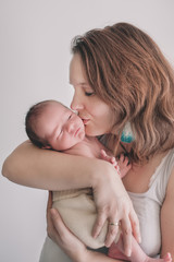 Mother holding her newborn baby in her arms and gently kissing his cheek.