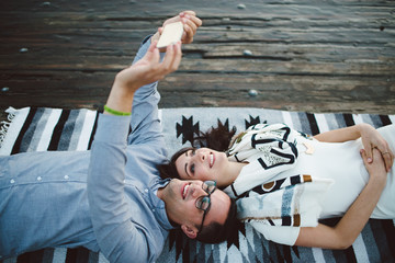 Young  couple laying on dock taking selfie with their phone