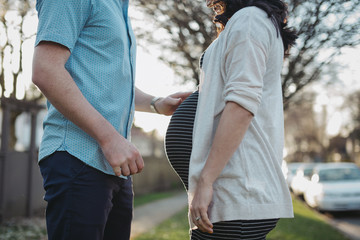 Man and pregnant woman standing together outside on sunny day