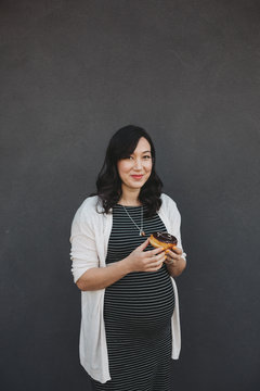 Young pregnant woman eating chocolate doughnut