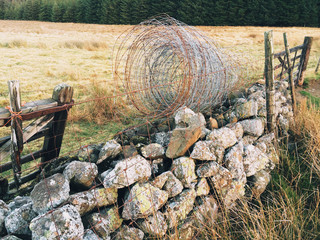Wire and fencing on a dry stone wall. Cumbria, UK.