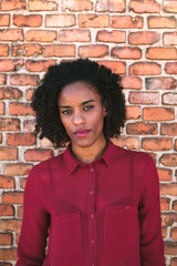 Young African Woman Leaning on a Brick Wall
