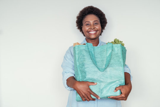 Smiling young African woman standing at home with groceries