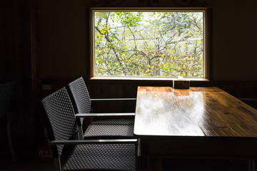 Table and chair in dark room beside bright window with view of trees