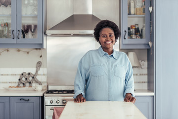 Smiling young African woman standing in her kitchen