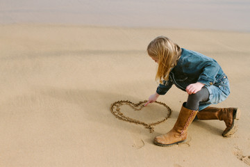 A little girl drawing a heart in the sand on a beach