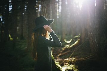 Girl adjusts hat under the sun in forest