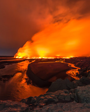 Glowing red lava meets flowing river
