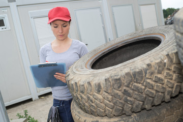 mechanic woman surrounded by tyres with clipboard