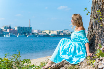 A middle-aged woman, plus in a light blue dress, rests on a city waterfront on a day off. The concept of femininity and romance in the city bustle