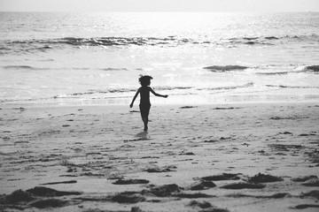 young boy runs towards the ocean at the beach