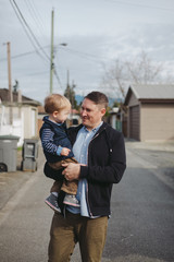 Young dad holding toddler boy outside on street