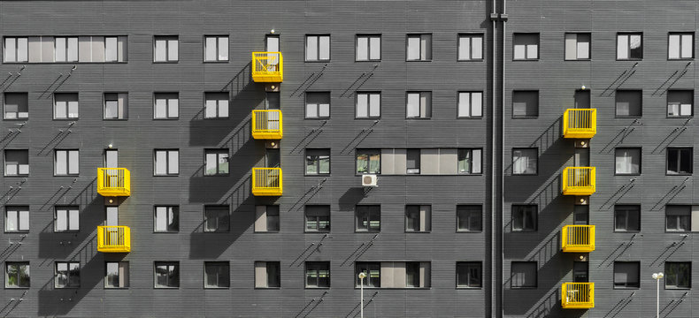 Exterior of gray residential building with yellow balcony