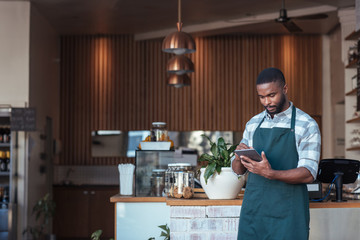 Young African entrepreneur using a tablet in his cafe