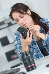 female photographer cleaning lens and camera