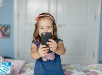 Cute young girl taking picture of herself with a smartphone