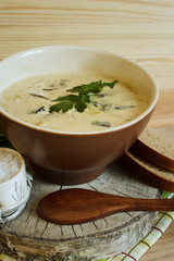 Soup with forest mushrooms on cream, with rye bread and parsley. Natural wood background. Selective focus. Vertical.