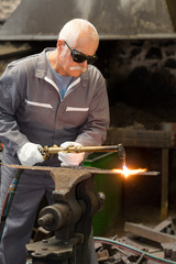 Senior metalworker using gas torch