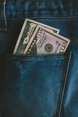 Close-up of US dollar bills inside a jeans pocket