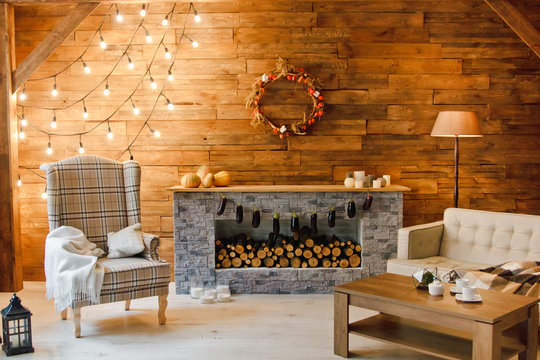 Home comfort. Armchair near the fireplace with firewood. Photo of interior of room with a wooden wall, wreath and garlands, Christmas atmosphere