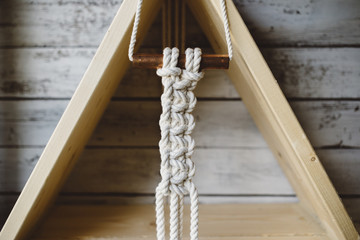 Macrame hanging from wood triangle shelf