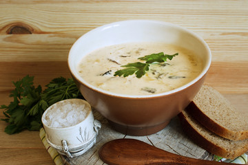 Serving soup from forest mushrooms in a rural style. Natural wood background. Selective focus. Horizontal.