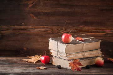 Autumn still life with old books, apples, maple leaves on the wooden background