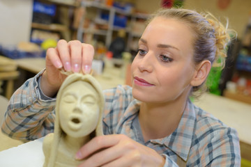 female sculptor creating