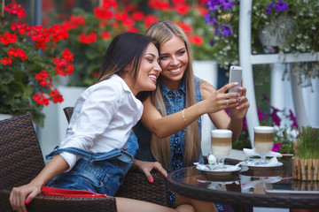 Group of girlfriends making a selfie photo at the mobile camera an smiling. Pretty women having fun at the cafe. Young girls laughing