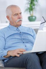 casual senior man sittingholding his laptop