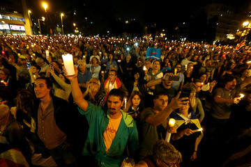 People hold candles during a gathering to protest against the imprisonment of leaders of two of the largest Catalan separatist organizations who were jailed by Spain's High Court, in Barcelona