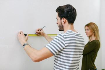 Young couple measuring the wall to hanging a picture.