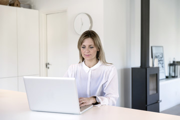 Businesswoman working on computer in black and white living space