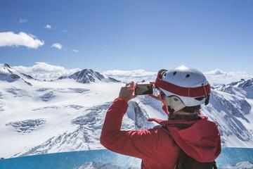 Skifahrerin macht ein Foto am Aussichtspunkt